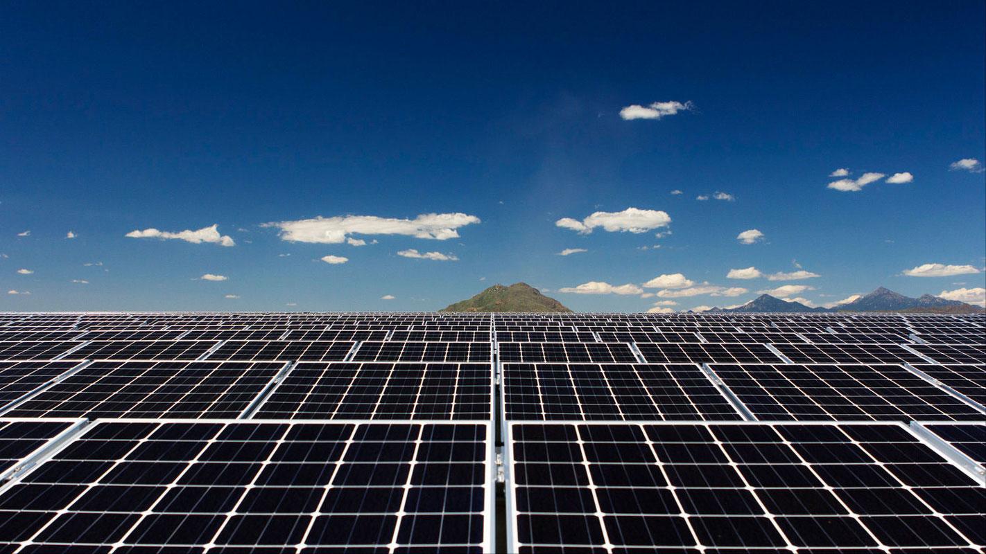 A képen egy napelemes rendszer látható egy hegy előtt.