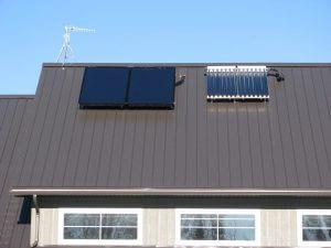 Síkkollektor és vákuumcsöves napkollektor egy tetőn.